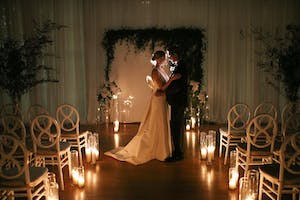 Bride and groom embrace in a candlelit Weill Music Room, surrounded by greenery and white orchids