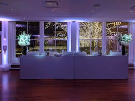 A festive bar awaiting guests in the Weill Terrace Room, terrace holiday lights in the background