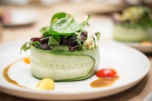 Cucumber-wrapped salad garnished with grape tomato halves and vinaigrette