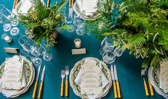 Teal tabletop set with bamboo-handled flatware, floral patterned china, and lush fern centerpieces