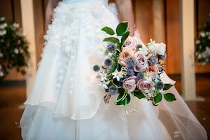 Bridal bouquet of lavender and blush roses, blue globe thistles, Star of Bethlehem, and greenery