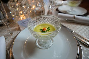 Chilled summer soup in a crystal bowl with an orange floral garnish