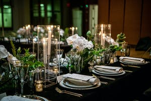 King's dining table set with black linen, white china, candles, white orchids, and greenery