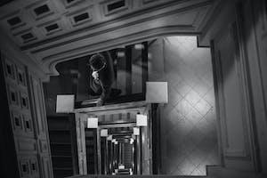 Groom walking down an open monumental staircase inside Carnegie Hall