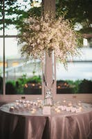 Escort card display on silver tabletop with dramatic sprays of white orchids