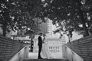 Bride and groom embrace on stairs to the Weill Terrace under a canopy of trees