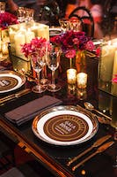 Faux black lacquer King's dining table set with gold décor and bunches of deep pink and red blooms
