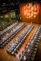Long banquet tables with gray linen, white floral arrangements, and candles in the Weill Music Room