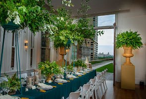 Soaring greenery on a May Room dinner table, Central Park visible through the open doors