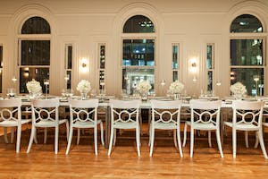 Historic arched windows are the backdrop for a modern white banquet table in the May Room