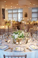 Pale blue table tops glowing with candlelit glassware and white florals fill the Weill Terrace Room.