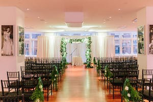 Wedding ceremony seating faces a chuppah laden with white blossoms and rich greenery.