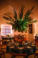 Summer dinner tables adorned with garden blooms and soaring greenery fill the Weill Terrace Room.