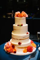 Four-tier wedding cake adorned with peonies, dahlias and ranunculus in peach, coral, orange and red.