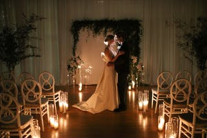 Bride and groom embrace in a candlelit Weill Music Room, surrounded by greenery and white orchids.