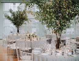 Foliage centerpieces soar above neutral elegant wedding reception tables in the Weill Music Room.