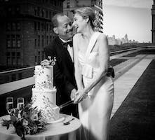 A bride and groom cut their wedding cake outside of the May Room, Central Park in the background.