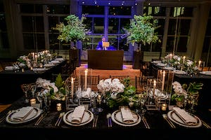 Elegant black banquet tables, a DJ, and large arrangements of greenery glow in the Weill Music Room