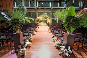 A view down the aisle in Weill Music Room, ceremony seats flanked by palm leaves