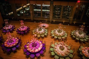 Violet and apple-green gala dinner tables in the Weill Music Room with candelabra and gold touches