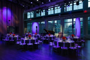 The Weill Music Room set for dinner with a concert grand piano awash in electric blue light