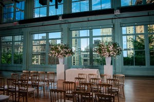 The Weill Music Room set for a mitzvah ceremony with lush pink florals and a skyline backdrop