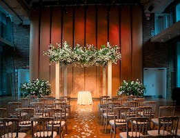 Ceremony seating faces a glowing chuppah with white blossoming branches in the Weill Music Room