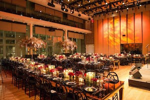 The Weill Music Room glows orange, set with black gala dinner tables and gold décor touches