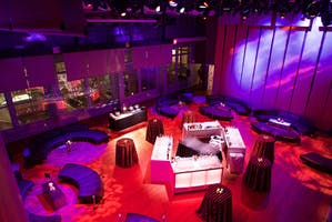 Illuminated white bars and black lounge seating in the Weill Music Room, washed in colorful light