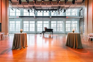 A reception featuring a grand piano silhouetted against a wall of windows in the Weill Music Room