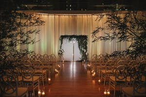 Flowing ivory drapes and lush greenery glow in candlelight for a wedding in the Weill Music Room