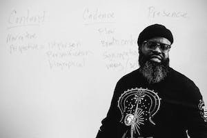"Black Thought talks in front of a white board that reads ""content,"" ""cadence,"" and ""presence."""
