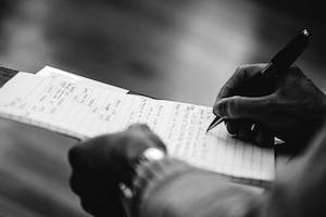 A close-up shot of two hands, one holds a pad of paper while the other uses a pen to write lyrics.