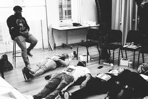 Black Thought sits above three participants, who are lying on the ground and working on breathing.