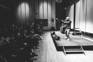 A workshop participant performing in front of a packed house during the showcase.