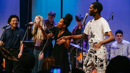 Teen musicians of the Future Music Project Ensemble sing and dance together during a performance.