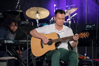 A man wearing a white polo and green pants smiles as he plays the guitar in front of a drum set.