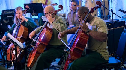 Two men and a woman play the cello with backup musicians at Sing Sing Correctional Facility.