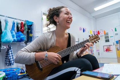 A young woman smiles playing the ukulele in a classroom.