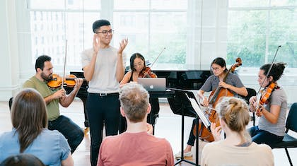 A man seated in a chair plays violin as another man standing next to him claps, and a woman plays violin while another plays cello as a small audience watches.