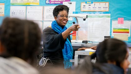 In an elementary classroom, a Black woman with a thick blue scarf smiles and points toward children.