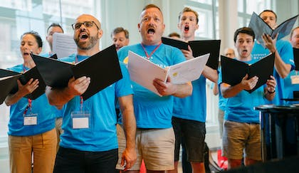 Adults in bright blue t-shirts sing together with binders of music in hand.