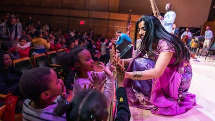 Three young children press their hands against Falu's at the front of the stage in Zankel Hall.