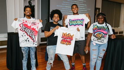 Four teens proudly display spray-painted white t-shirts with bright colors in the Weill Terrace Room.