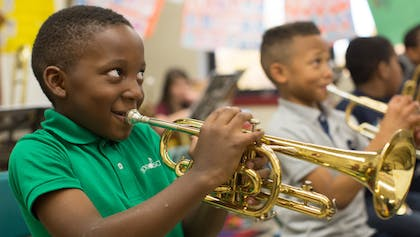 A small Black child with a bright green shirt smiles while playing the trumpet in a classroom.