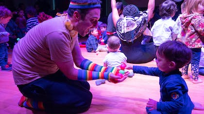 A male actor with a rainbow headband, gloves, and socks shows a toddler toys in purple-hued light.