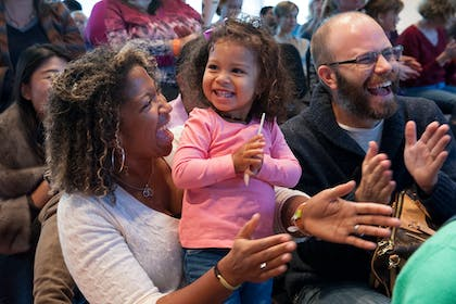 A Black woman smiles at a happy toddler close to her; a White man with glasses laughs nearby.