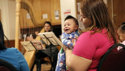 A woman in a pink shirt looks adoringly at a toddler in a onesie; a harpist sits in the background.