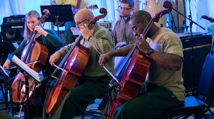 Two men in glasses and green pants and a woman play the cello at Sing Sing Correctional Facility.