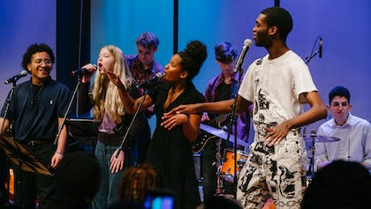 Teenage musicians of the Future Music Project Ensemble sing and dance together during a performance.